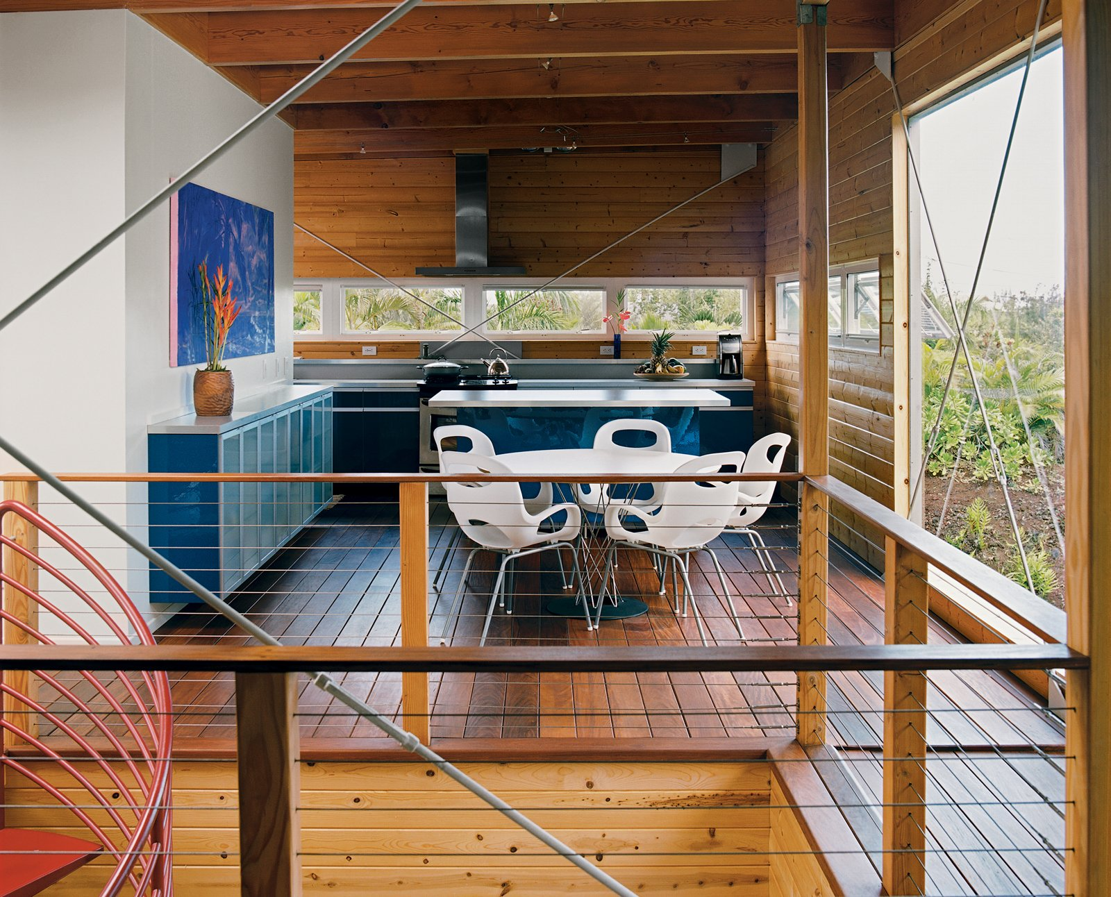 The home's upper floor features copious amounts of untreated pine. Five large cross-braces keep the timber frame rigid. The royal blue Ikea kitchen, Noguchi Cyclone dining table for Knoll, and Karim Rashid Oh chairs for Umbra all made the trip from the mainland in a twenty-foot-long shipping container. Above the wall-mounted credenza, a colorful painting of the Puma moonrise is by local artist Arthur Johnson. Tagged: Dining Room, Table, and Chair.  Photo 4 of 9 in Lava Flow 4, The Big Island