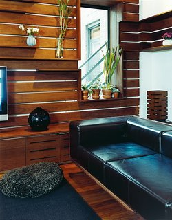 Ingenuity can compensate for a modest budget. The Zizmors removed the base from a mid-priced leather couch from West Elm and inserted it in a custom armature made with walnut veneer.