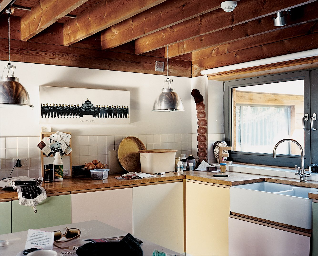 Kitchen The architects kept the low-beamed ceiling, retaining the house's English countryside charm. The kitchen features custom cabinetry designed by artist Neil Jolliffe. The couple purchased their Banksy prints from the artist's London gallery, Tom Tom.  Photo 3 of 7 in Heart of the Country
