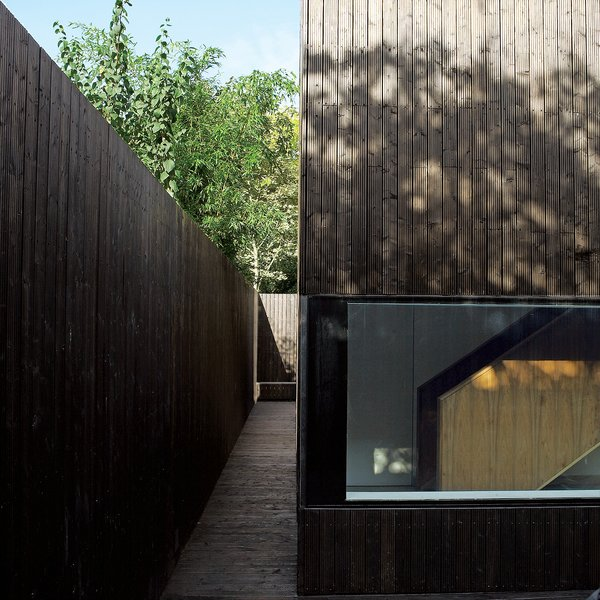 Exterior, House Building Type, and Wood Siding Material The outer walkway leads all the way around the structure, spilling into a small patio in back.  Photo 3 of 13 in All Clad