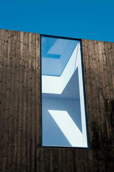 Exterior, Flat RoofLine, House Building Type, and Wood Siding Material Adjaye cut a gap straight through the roof and facade.  Photo 7 of 13 in All Clad