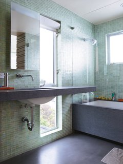 The vertical full-length window offers a slice of the outdoors in the custom-outfitted master bathroom (save for a tub and sink by Kohler; faucet and showerhead by Vola).