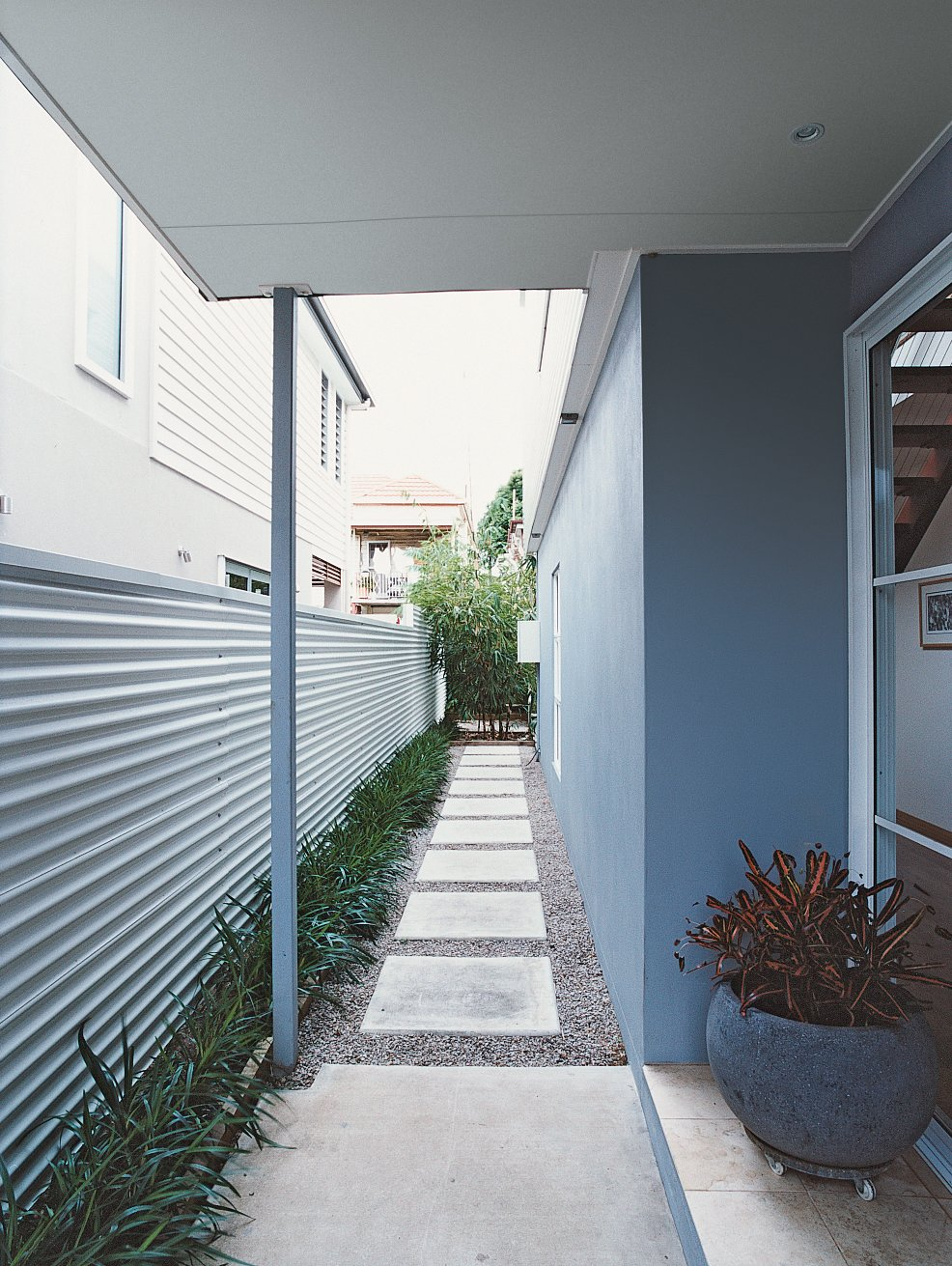 Side Yard, Hardscapes, Metal Fences, Wall, Horizontal Fences, Wall, and Outdoor Clayden made the most of his modest lot by building as close to the perimeter as local zoning codes allow.  Photo 3 of 8 in Minimalist Bachelor Pad in Brisbane