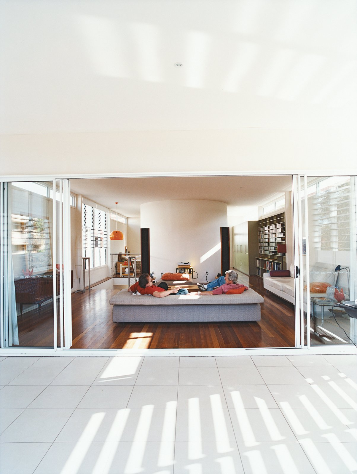Living Room, Medium Hardwood Floor, and Sofa Clayden and Sam Cutler, both former tour managers for rock bands, talk music in the spacious, uncluttered living room that opens onto the balcony.  Photo 4 of 8 in Minimalist Bachelor Pad in Brisbane