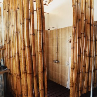 The six-by-six-foot shower boasts a hardwood-slatted deck, which allows water to seep into a concrete pan that empties into the main drainage system. The cage of bamboo poles provides the requisite privacy to the bather.