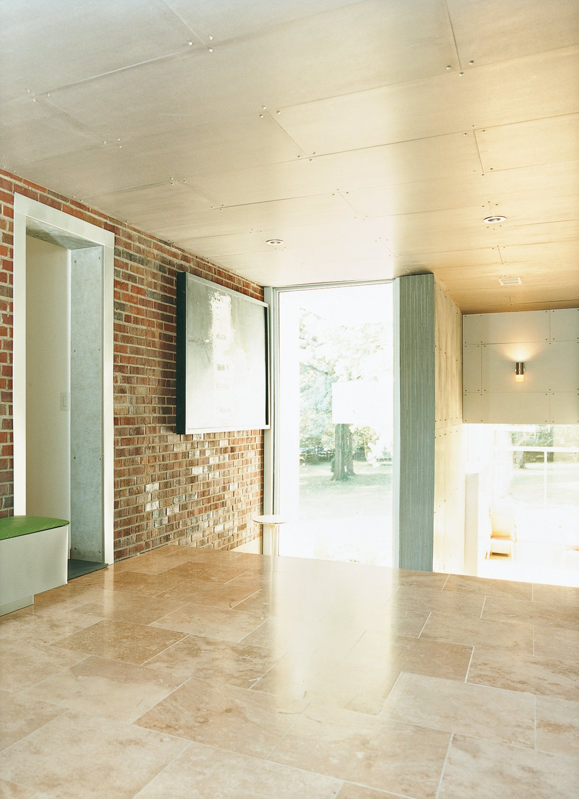 An area that once led from the original house to the garage is now enclosed and serves as a transitional space between the private and public areas of the house.  Photo 6 of 9 in Home Schooled