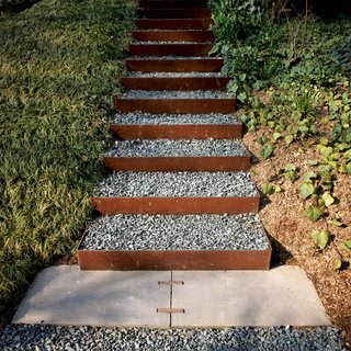 The stairs going up the knoll to the roof garden and to the house's second-level entrance are made from Cor-Ten steel risers (which develop a rich, rusted patina) and filled with gravel in order to create a nonslip surface that drains well. Steel and steelwork by Virginia Industrial.