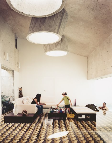 Three protruding concrete skylights brighten this living room, despite the graphic floor tile and dark ceiling.