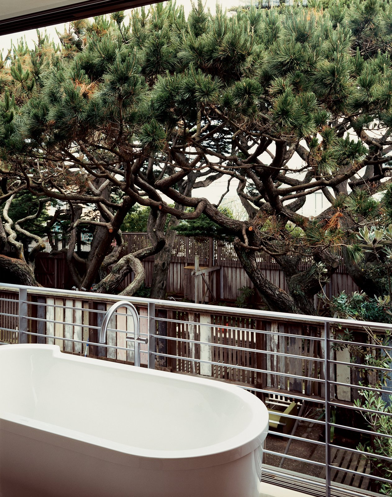 Outdoor, Hot Tub Pools, Tubs, Shower, Trees, Wood Fences, Wall, and Vertical Fences, Wall Sliding glass panels in the bathroom open to put the tub in the tree canopy.  Photo 5 of 13 in This Surfer's Beach House is More Than It Seems