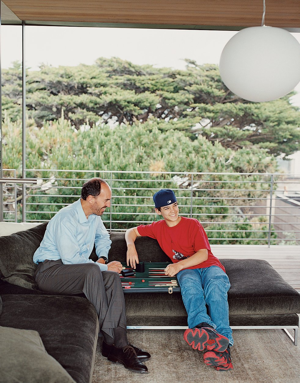 When not surfing, Lloyd-Butler and his son John repose in the new addition over a game of backgammon. Tagged: Living Room, Sofa, and Pendant Lighting.  Photo 6 of 13 in This Surfer's Beach House is More Than It Seems