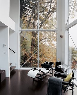 A Corbusier chaise and Eileen Gray end table fill out the corner of the couple's high-ceilinged living area, which helps create the desired loftlike feel of the home.