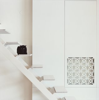 This uniquely shaped staircase connects a main floor to a mezzanine above in an apartment in Vilnius, Lithuania, that was renovated by architect Rytis Mikulionis. The treads give the illusion of having been created from peeled-down pieces of white steel, then topped with MDF board that's been painted white.