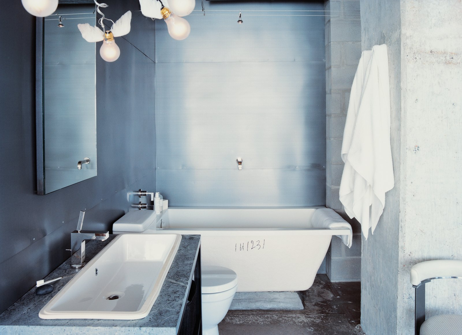 Bath Room, Freestanding Tub, Ceiling Lighting, Drop In Sink, and Concrete Wall Winged light bulbs, part of an Ingo Maurer fixture, bring levity to Hill's bathroom. The space features a zinc wall by Houston metalworker George Sacaris, who also did the bathroom and kitchen cabinets.  Photo 6 of 10 in 10 Ideas For the Minimalist Bathroom of Your Dreams from Stripped Ease