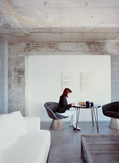 With bright red hair, Hill is a standout in a gray-glass 1960s building. Her coffee table is a French mail-sorting table with the legs cut down.