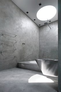 8 Inspiring Minimalist Bathrooms - Photo 2 of 7 - This coolly modern sanctuary in Denmark echoes the elegant austerity of resident Nick Zappon's films. The master bathroom was constructed in concrete with a circular bathtub and accompanied by a parallel circular cutaway in the roof that allows contemplative bathers to view the stars from the tub.