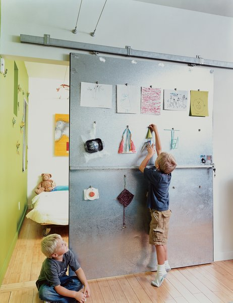 Doors, Sliding Door Type, Interior, and Metal David Baird designed the custom sliding doors with materials and hardware from Home Depot. The doors also act as a makeshift critique wall for Bo and Sky's artwork.  Photo 6 of 13 in Baton Rouge Oasis