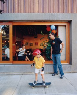 Community Building - Photo 8 of 10 - Resident Brooks Jordan and his son Leif take some time out to play outside the Belmont, where a steady stream of pedestrians and diners lend the building an inviting feel.