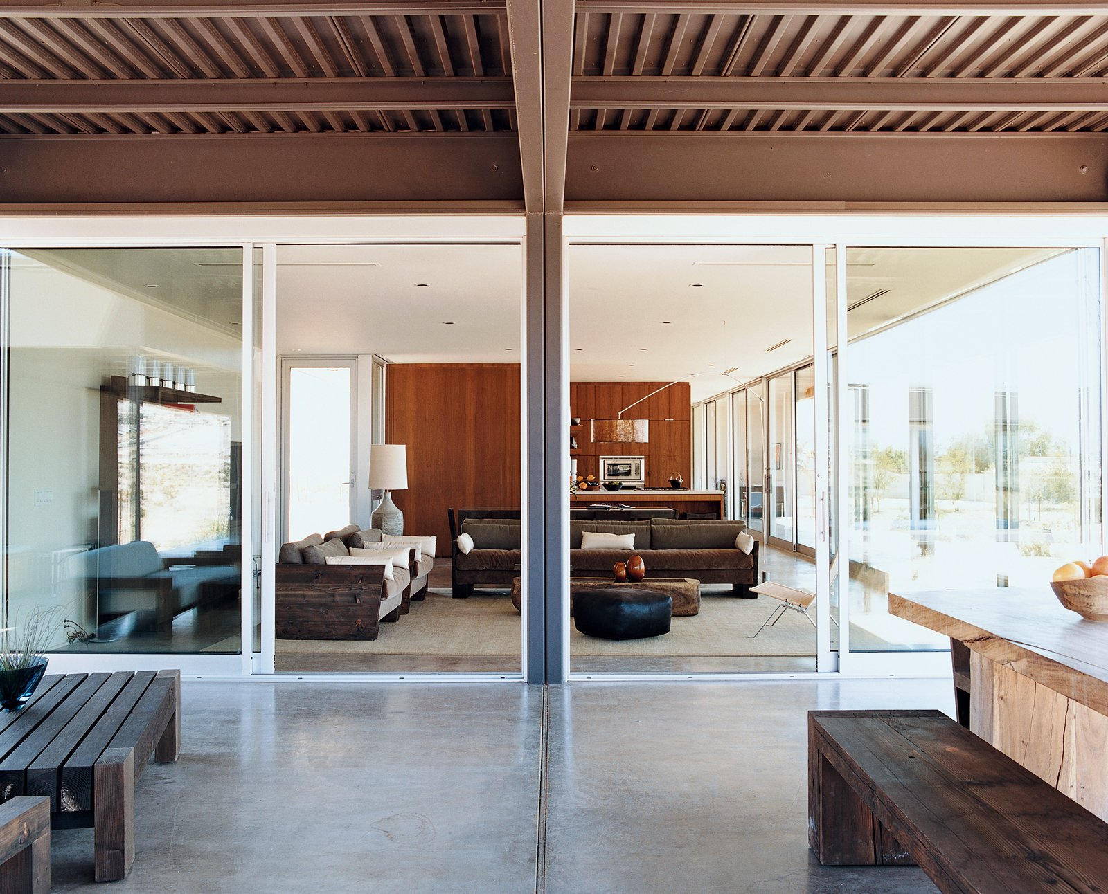 Dining Room and Concrete Floor There are generously proportioned nine-foot-high ceilings throughout the Desert House. Marmol Radziner designed and built the outdoor table and benches from reclaimed Douglas fir.  Photo 8 of 9 in Desert Utopia