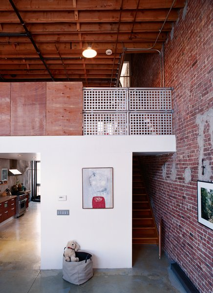 By leaving the exterior walls of the neighboring structures exposed on their interior, Miro and Weiss guaranteed that the neighborhood's history would be a part of their new home. Raw plywood and industrial-strength steel railings are balanced with custom finishes and signs of domesticity.  Photo 4 of 5 in A House Grows in Brooklyn