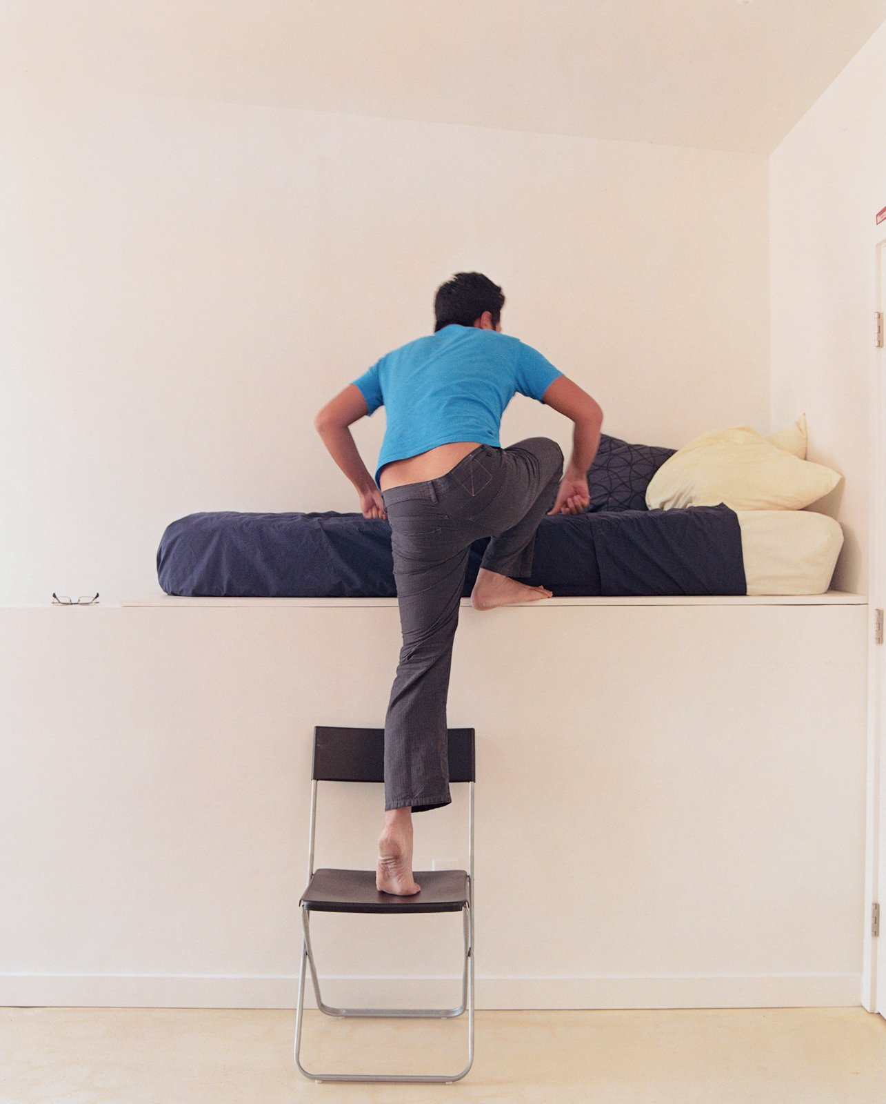 Jeremy Claud ascends to his bed, which is on a raised platform that hovers over a staircase.  Photo 5 of 11 in New Orleans, LA