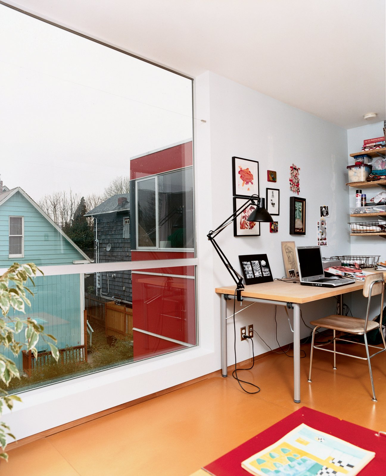 Sarti's upstairs office provides a cozy corner for work and relaxation. The large windows allow him to search the surrounding backyards for inspiration when stuck in a rut.  Photo 4 of 8 in Halving It All