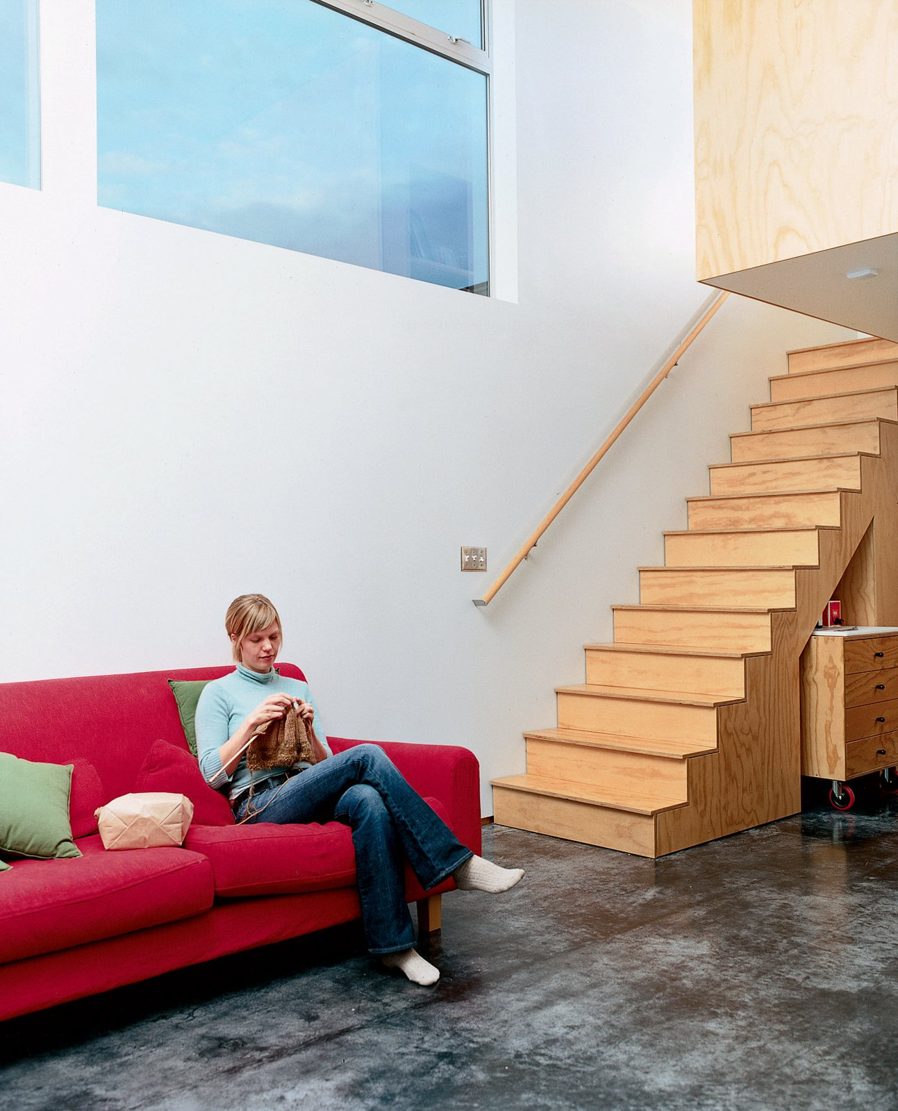 """David's wife, Jodi, knits it up on the IKEA couch. The floor color, Sarti explains, """"comes from the natural efflorescence that occurred as the concrete cured.""""  Photo 5 of 8 in Halving It All"""