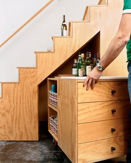 A mobile bar cart with room for kitchen storage is not the most traditional under-stair solution, but it's proven to be critical in the design of this kitchen and living space in Seattle by designer David Sarti. Its plywood construction, black knobs, and bright red casters mean that this design is meant to be noticed rather than be ignored.