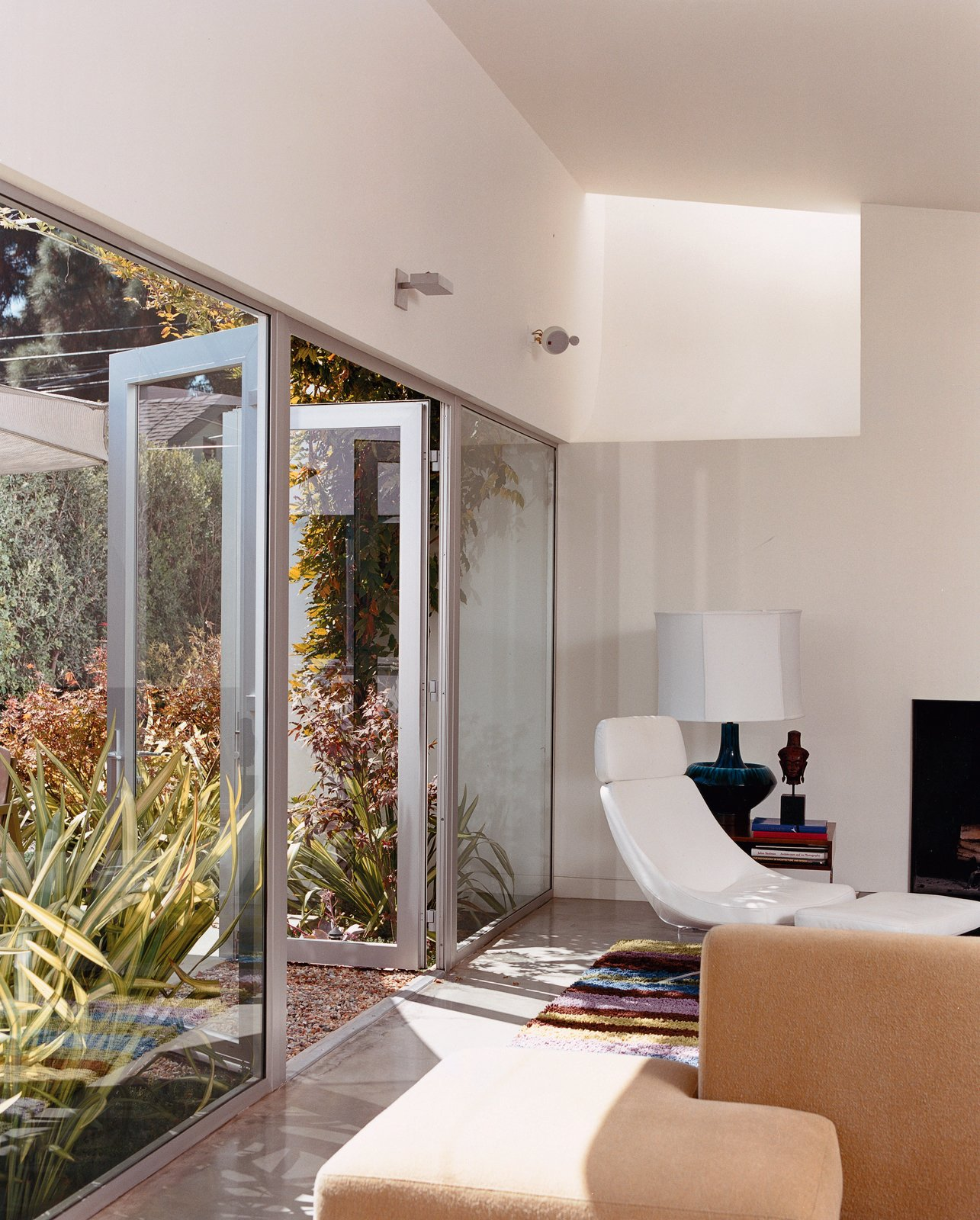Seven-foot-high glass doors bring the garden, landscaped by Jay Griffith, into the living room. A skylight brings even more light into the white-walled room with polished-concrete floors. There is a splash of color in a custom rug designed by Dawn Farmer and made by Della Robbia, which also made the sofas. Tagged: Living Room, Recliner, and Concrete Floor.  Photo 2 of 9 in Venetian Vicissitude