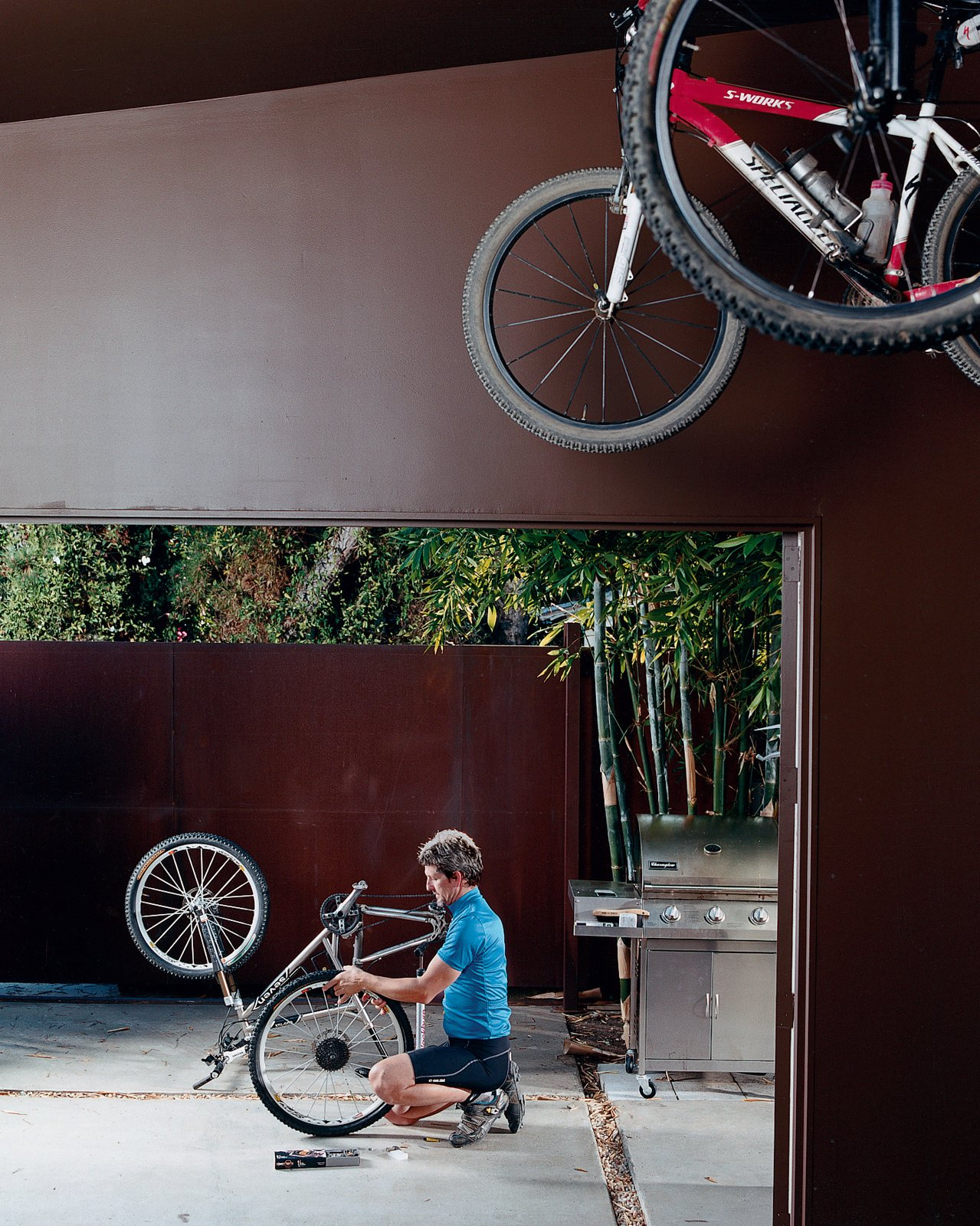 Outdoor, Large Patio, Porch, Deck, and Concrete Patio, Porch, Deck Pierre Kozely mends his bike on a patio in the rear yard, seen from their garage—which was transformed into a media room. Behind him is a Cor-Ten rolling gate that gives access   to the back alley.  Photo 7 of 9 in Venetian Vicissitude