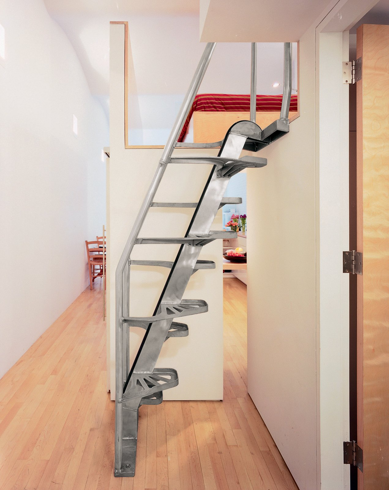 """""""The stair [by Lapeyre Stair] is very cost-effective, as compared to building woodwork,"""" Woo explains. """"It occupies very little space, and you can come down without holding the rail."""" Of the small gap that reveals the kitchen, he says, """"That's very important, to give a sense of continuous space.""""  Photo 7 of 7 in Big City, Little Loft"""