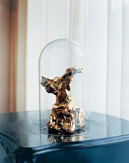 A gold-plated One Minute sculpture from the Personal Editions collection by Marcel Wanders under an antique glass dome.