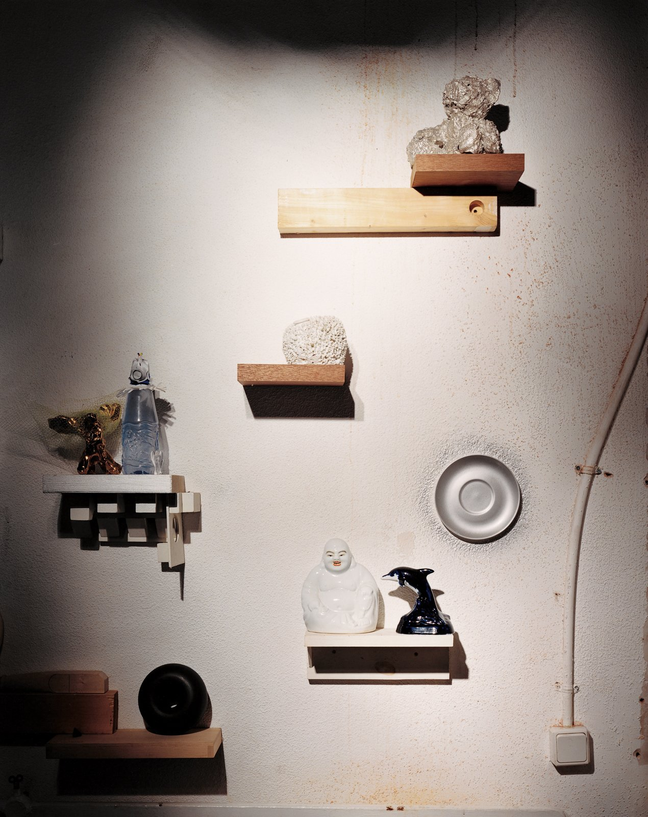 An installation of mismatched handmade shelves makes a display area for another enigmatic assortment of objects, including a Wanders Sponge vase (1997), made by soaking a real sponge in clay, which burns away when the piece is fired. The same technique was used on the silver-plated teddy bear above it. The dolphin and Buddha figures—perhaps a reminder of Wanders's role in mainstreaming kitsch—illustrate the designer's interest in ordinary, popular decorative objects.  Photo 10 of 11 in Marcel Wanders
