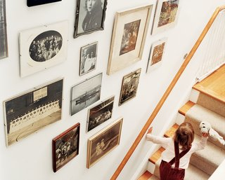 """Row House Revival - Photo 7 of 8 - """"You have all this history underneath you here,"""" says Matthew Bardin. A display of evocative old family photos, arranged in the stairwell, underscores Bardin's point."""