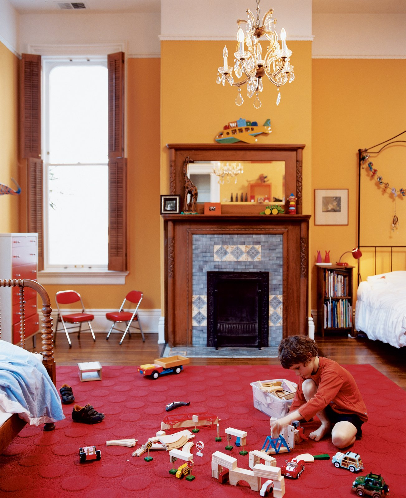 Kids Room and Bedroom Room Type In the boys' shared room, Jasper finds plenty of space to scatter toys. An original chandelier provides a reminder of the house's past while muted orange walls plant it firmly in the present.  Photo 7 of 8 in Taking Liberties