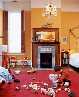 In the boys' shared room, Jasper finds plenty of space to scatter toys. An original chandelier provides a reminder of the house's past while muted orange walls plant it firmly in the present.