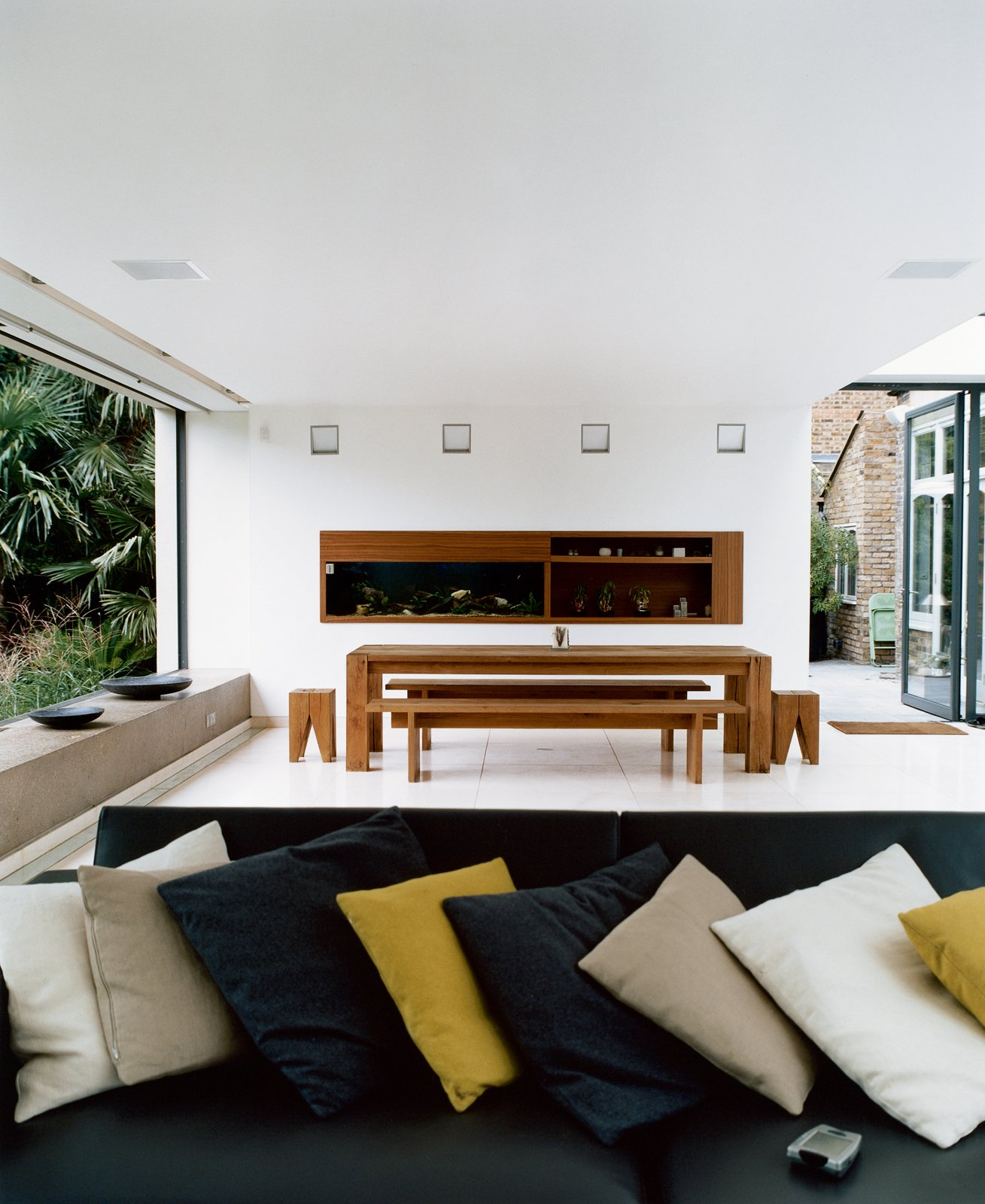 The new space was conceived as a blank canvas so that the decidedly nontraditional English garden—a large lawn bordered by exotic palms, bamboos, ferns, and other flamboyant foliage inspired by a recent holiday to Australia—could be the focal point. The minimalist dining table, benches, and stools are by e15.  Photo 5 of 10 in Victorian Secrets