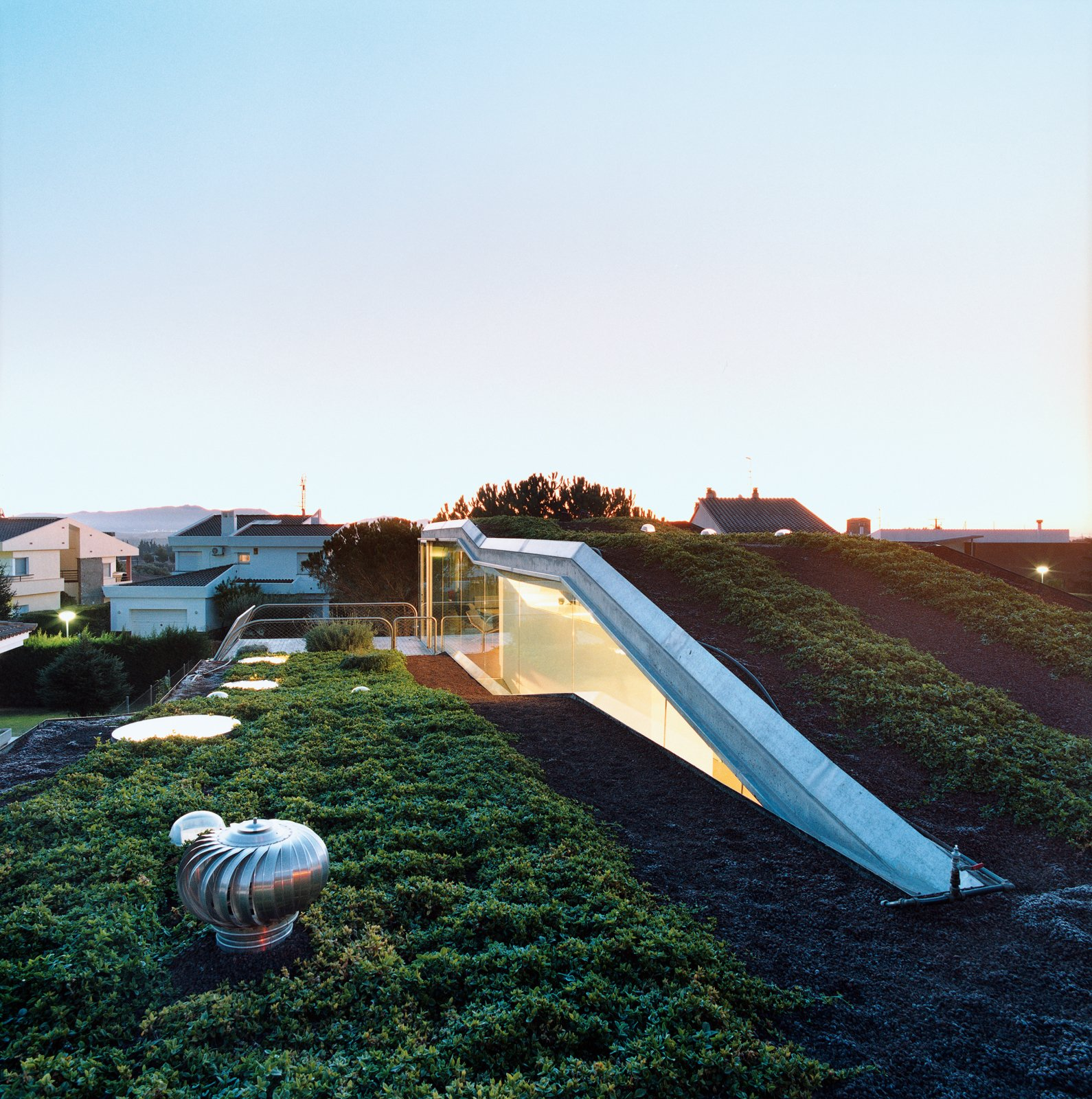Outdoor, Rooftop, Grass, and Gardens The hydroponic rooftop garden grows out of volcanic stones. The home is conceived as a giant C-shaped spiral.  Photo 1 of 10 in Suburban House of the Future by Cloud9