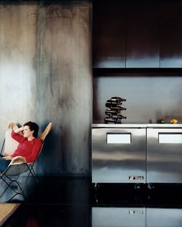 Cold-rolled steel walls lend a bluish tint to the kitchen, which features cabinetry made of NAP, or North American plywood, which is a very dense plywood with a natural chocolate-colored finish.