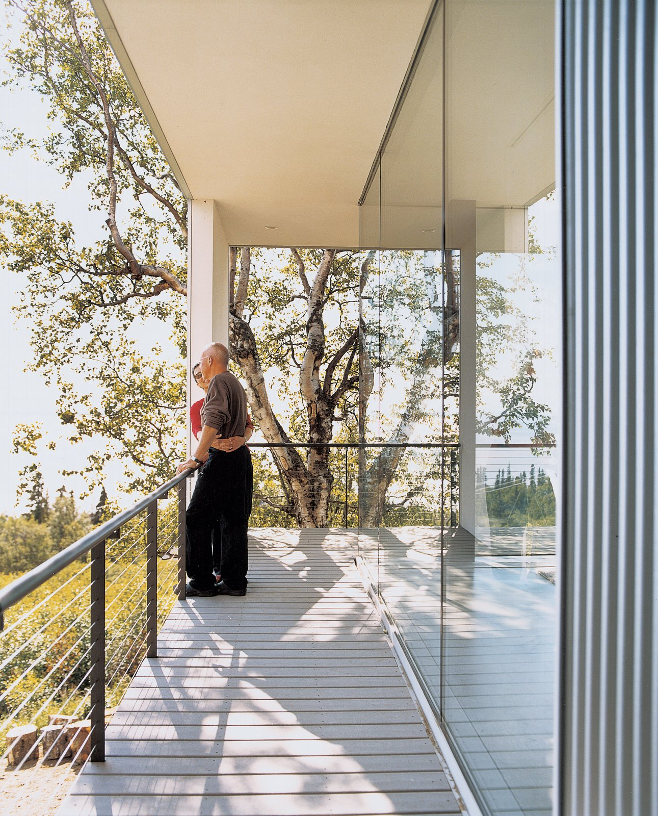 The whole house opens up to its surroundings with floor-to-ceiling windows that are perfect for nature gazing. Tagged: Outdoor, Wood Patio, Porch, Deck, and Small Patio, Porch, Deck.  Photo 2 of 9 in Alaska: The Final (Architectural) Frontier