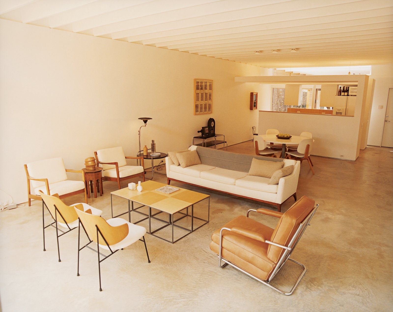The living room of Baum's 1650-square-foot home features a poured-concrete floor as well as many vintage finds and artifacts from his travels. The sidechairs in the foreground are by Ib Kofod-Larsen and the leather chair is by Gilbert Rohde.  Photo 2 of 9 in Bringing Families Back to Downtown Dallas