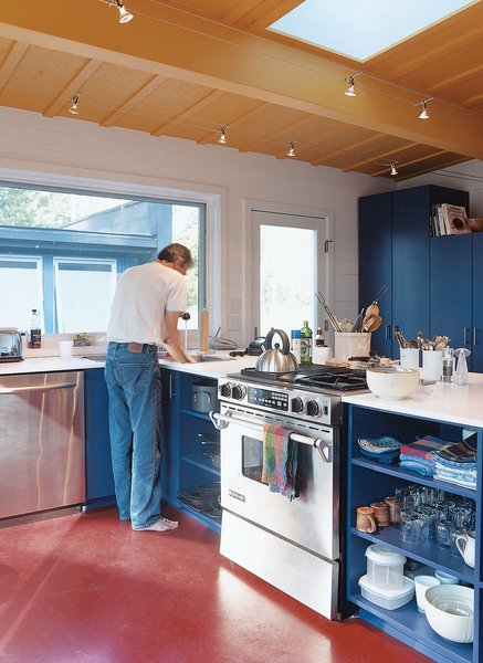 """Primary colors and uncomplicated spaces define the interiors of both sheds. Golob is shown above in the modest open kitchen, where appliances were chosen for """"cost, durability, and efficiency.""""  Photo 7 of 10 in Off the Beaten Path"""