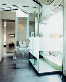 The dramatic bathroom features a glass sink designed and cast by Mies Grybaitis of OIA. The etched glass shower is accented by green glass tile.