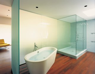 A translucent wall silhouettes a Duravit bathtub by Philippe Starck in the master bathroom.