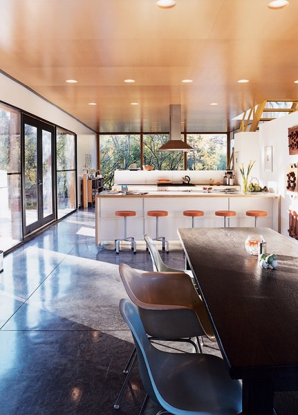 """It was a major decision to put the kitchen in the center where everything would revolve around it,"" says Lazor. ""We did this simply by following what patterns we observed—it was just where people gravitated."" The bar stools are by Blu Dot, and the chairs by Charles and Ray Eames."