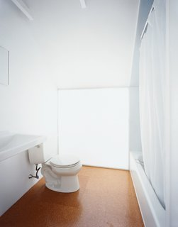Upstairs, simple porcelain pieces such as a Kohler toilet adorn the modest master <br><br>bathroom. Beneath the downward-pitched ceiling, a polycarbonate-panel wall brings in light from the south-facing skylight behind.
