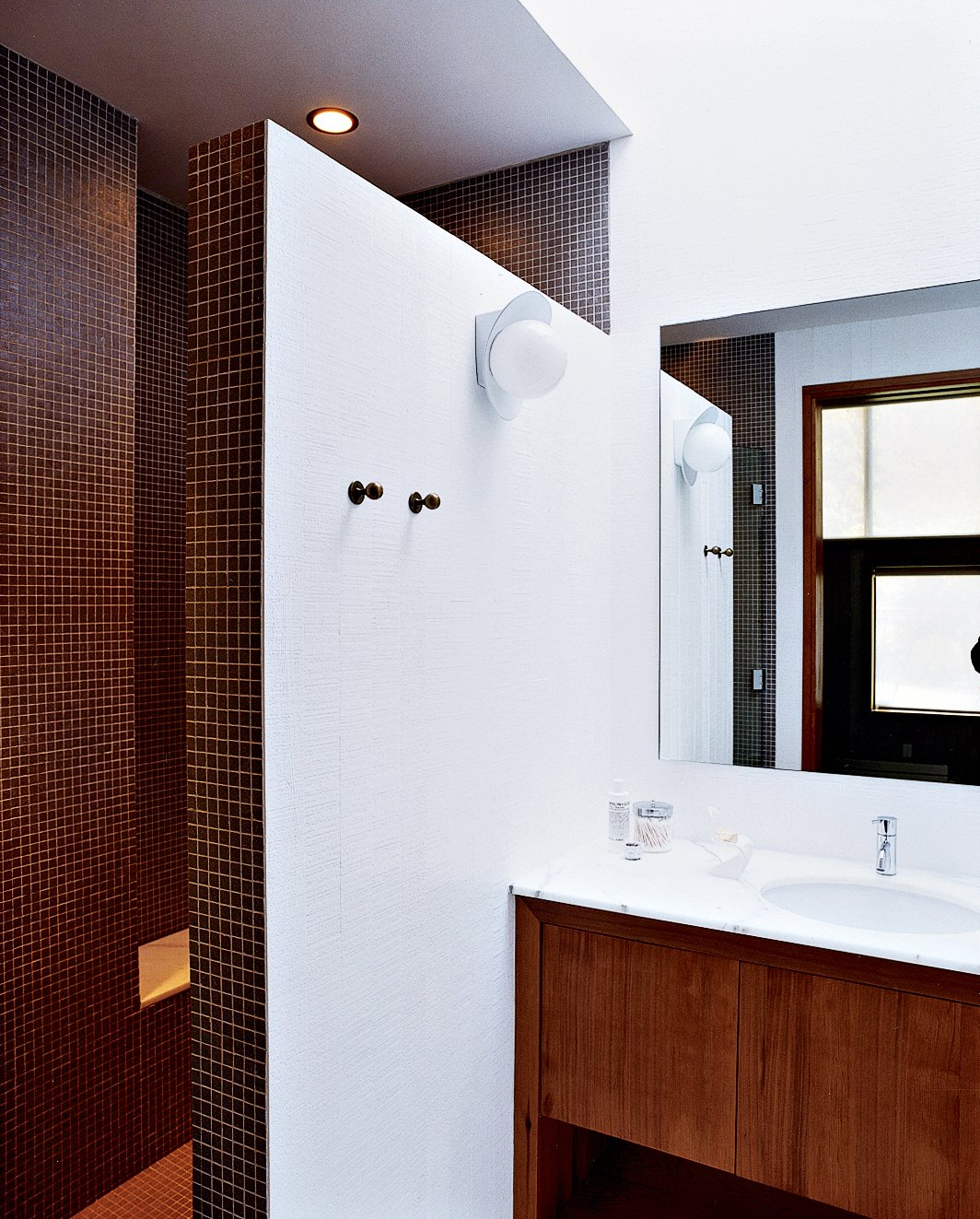 Bath Room, Marble Counter, Enclosed Shower, Full Shower, Ceiling Lighting, and Ceramic Tile Wall A double-size shower, clad floor-to-ceiling in tiny earth-toned tiles, was built after relocating the water heater and claiming its space. A chic yet discreet toilet is wall-hung and the tank concealed, greatly ameliorating the somewhat claustrophobic feel of the original bathroom.  Photo 5 of 6 in The Pace of Portland