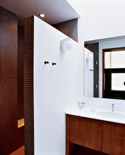 A double-size shower, clad floor-to-ceiling in tiny earth-toned tiles, was built after relocating the water heater and claiming its space. A chic yet discreet toilet is wall-hung and the tank concealed, greatly ameliorating the somewhat claustrophobic feel of the original bathroom.