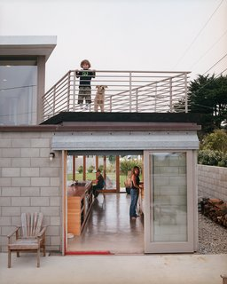 The couple's son Dylan and dog Petra enjoy the deck while Mary Kate and Thomas work in the kitchen below. Sliding doors open to the outdoors on both sides.
