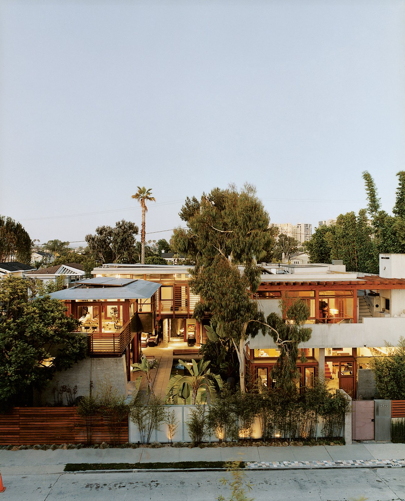The exuberant results of Hertz's design are visible from the street. Giant birds   of paradise, king palms, and bamboo tower above the fence. The Balinese long building, seen on the far left, is almost nautical; on the right, the original house's rammed-earth entry wall frames its concrete layers.  Photo 6 of 6 in Sustainability in Stages