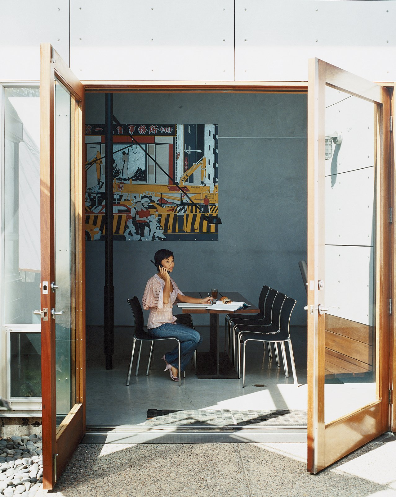 """May Lawrence sits at the dining table, which features mahogany planks attached to an actual I beam. Above her sprawls a Rigo 99 painting of a bustling Taipei street scene, which according to Ward helps import some """"city energy"""" into the suburbs.  Photo 7 of 14 in 12 """"Pro-Tips"""" For Installing Wallpaper in Your Home from The New Suburbanism"""